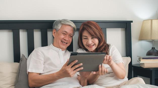 Pares sênior asiáticos usando a tabuleta em casa. as avós chinesas sênior asiáticas, o marido e a esposa felizes após acordam, vendo o filme deitado na cama no quarto em casa no conceito da manhã. Foto gratuita