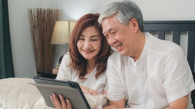 Pares sênior asiáticos usando a tabuleta em casa. as avós chinesas sênior asiáticas, vídeo-chamada que falam com neto da família caçoam ao encontrar-se na cama no quarto em casa no conceito da manhã. Foto gratuita