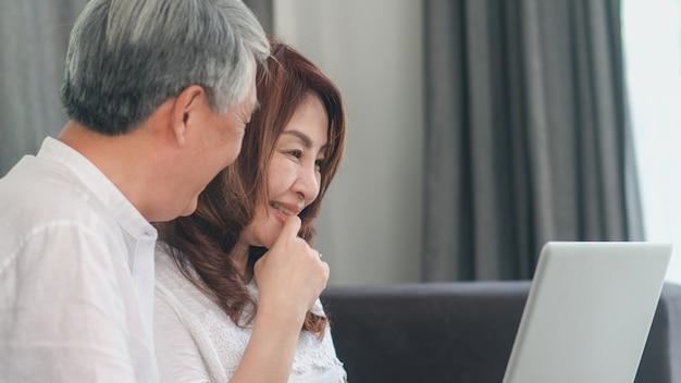 Pares sênior asiáticos usando o laptop em casa. as avós chinesas sênior asiáticas, surfam o internet para verificar meios sociais ao encontrar-se no sofá no conceito da sala de visitas em casa. Foto gratuita