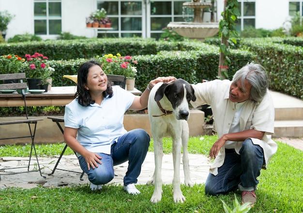 Pares superiores que jogam com o cão grande no jardim home. Foto Premium