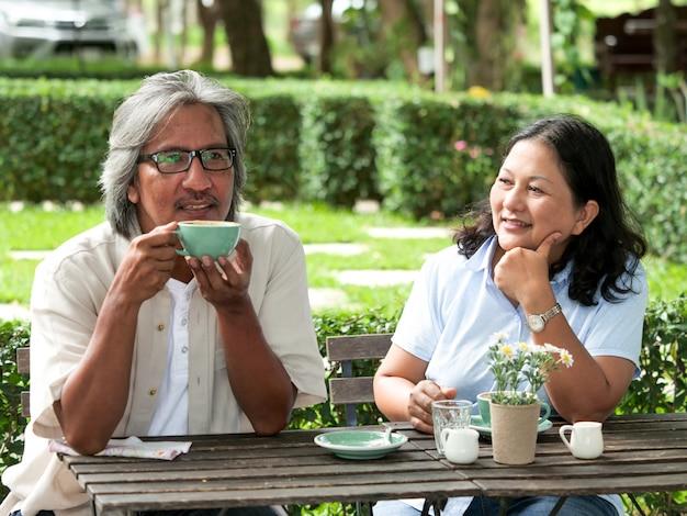 Pares superiores que riem ao beber o café no jardim home. Foto Premium