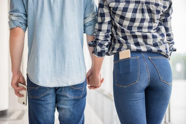 Pares vestidos ocasional que mantêm as mãos unidas. Foto Premium
