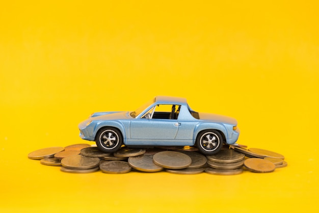 Parque de estacionamento modelo azul em moedas de ouro de pilha Foto Premium