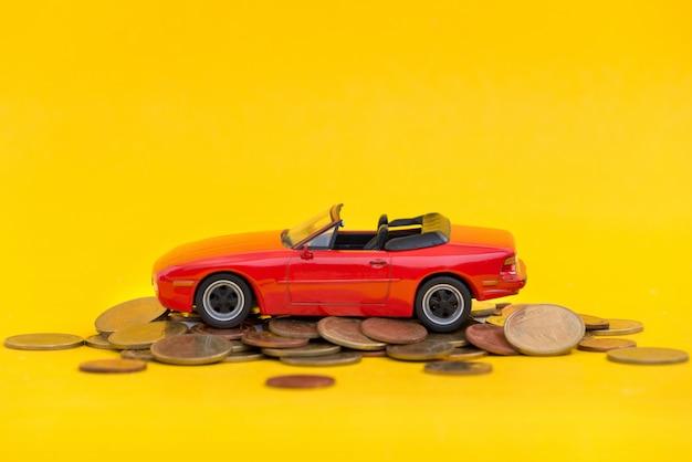 Parque de estacionamento vermelho modelo em moedas de ouro de pilha Foto Premium
