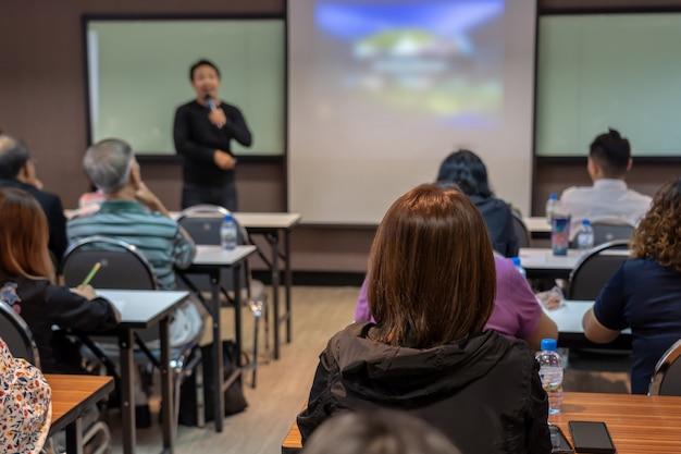 Parte de trás do público ouvindo o alto-falante asiático com roupa casual no palco em frente Foto Premium