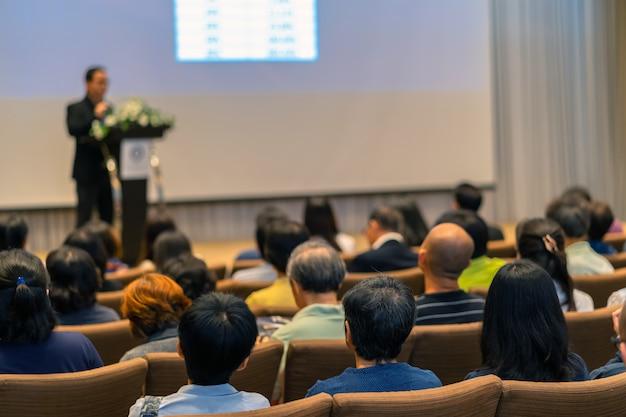 Parte de trás do público ouvindo o alto-falante com pódio no palco na conferência hal Foto Premium