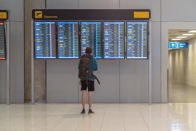 Parte de trás do viajante com a bagagem em pé sobre a placa de voo para o check-in Foto Premium