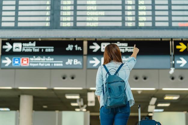 Parte de trás do viajante mulher asiática com pé de bagagem sobre a placa de vôo para check-in Foto Premium