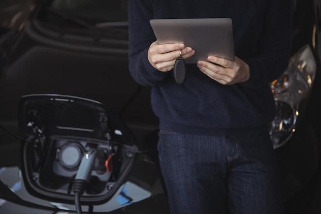 Parte média do homem usando tablet digital enquanto carrega o carro elétrico Foto gratuita