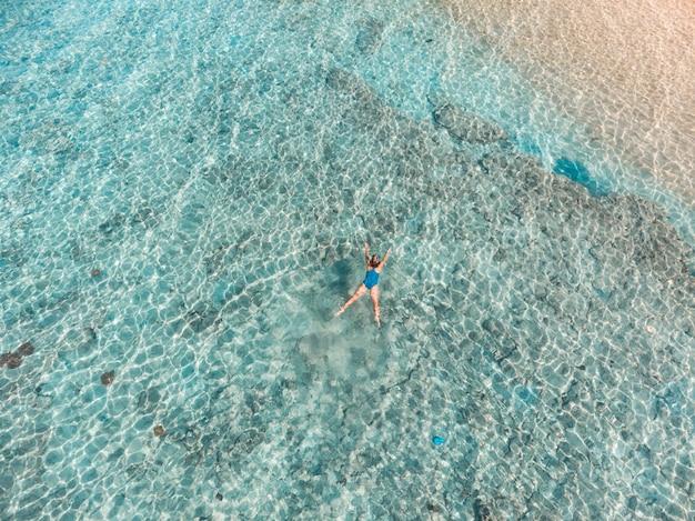 Parte superior aérea abaixo dos povos que mergulham no mar das caraíbas tropical do recife de corais, água azul de turquesa. arquipélago de indonésia wakatobi, parque nacional marinho, destino de viagem de mergulho turístico Foto Premium