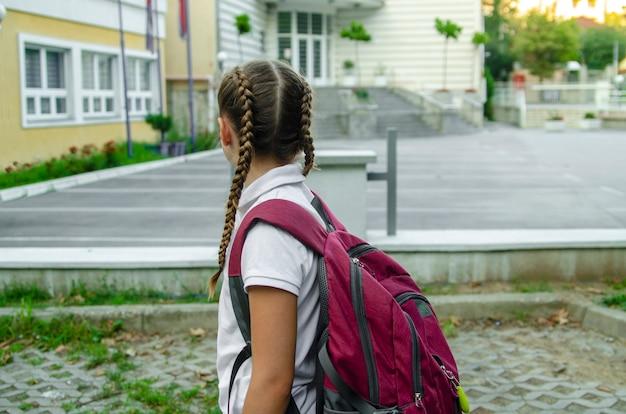 Parte traseira da criança da menina que vai à escola com a trouxa vermelha. Foto Premium