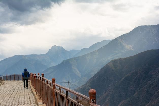 Parte traseira de uma caminhada do homem na ponte pelo lado da montanha alta do verde da escala em lijiang, china. Foto Premium