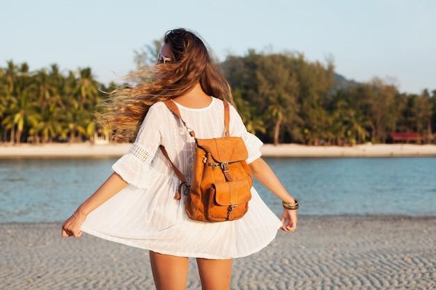 Parte traseira de uma linda mulher vestida de branco andando despreocupada na praia tropical com mochila de couro. Foto gratuita