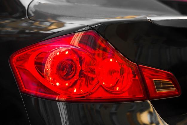 Parte traseira do carro escuro com luz traseira vermelha Foto gratuita