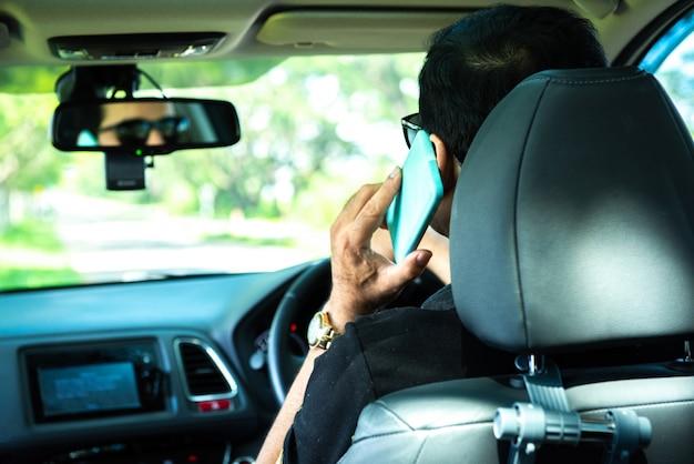 Parte traseira do homem usar telefone móvel esperto no carro Foto Premium