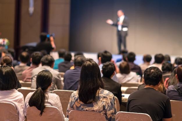 Parte traseira do público sentado e ouvindo os speackers no palco Foto Premium