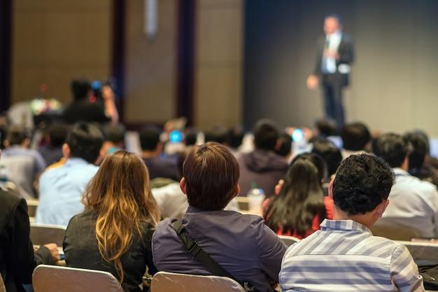Parte traseira do público sentado e ouvindo os speackers Foto Premium