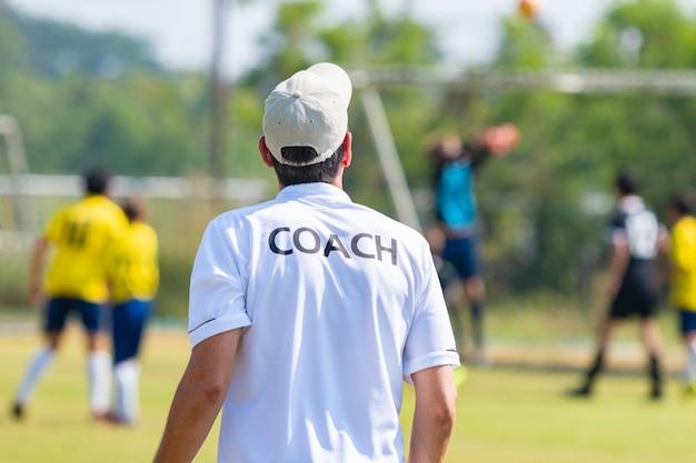 Parte traseira do treinador de futebol vestindo branco camisa do treinador treinando sua equipe durante um jogo Foto Premium