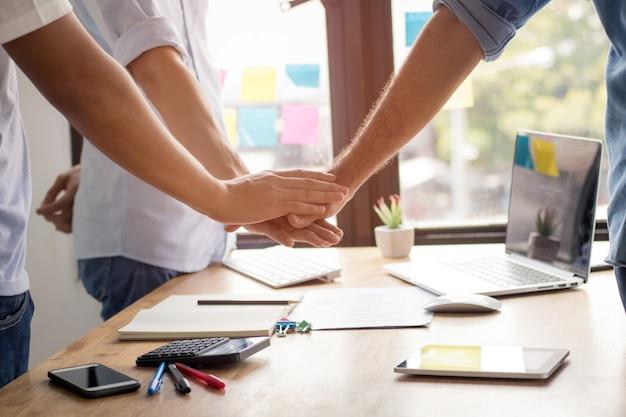 Parthnership e trabalho em equipe conceito, empresário leve a coordenação de mão sobre a mesa Foto Premium