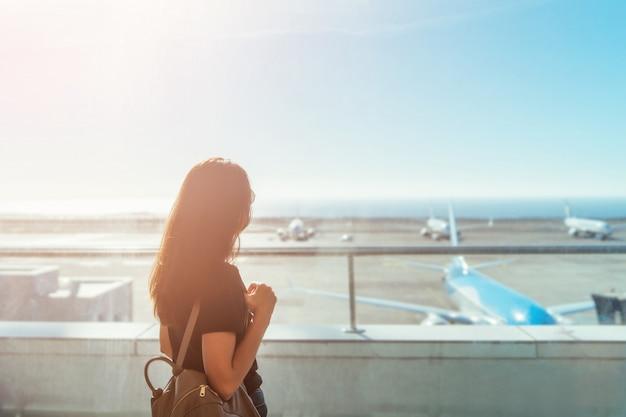 Partida de espera da menina longa moreno do cabelo no aeroporto. Foto Premium