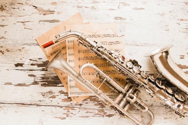 Partituras sob saxofone e trompete Foto gratuita
