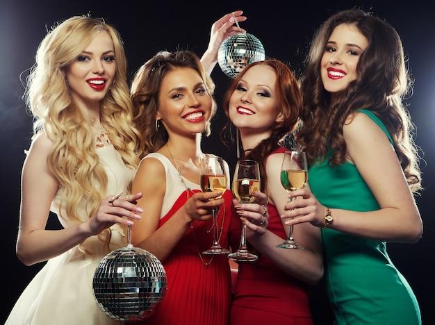 Party girls tinindo flautas com vinho espumante Foto Premium