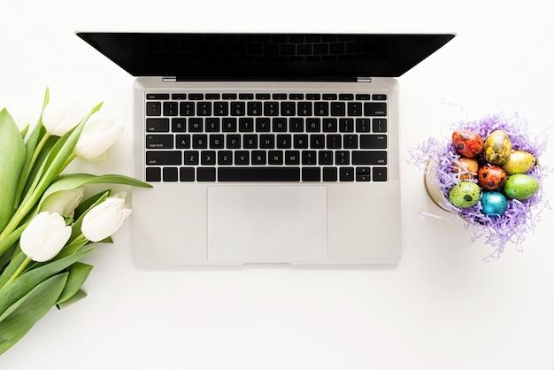 Páscoa, conceito de primavera. vista superior da simulação de computador laptop, flores de tulipa branca e ovos de páscoa em um balde Foto Premium