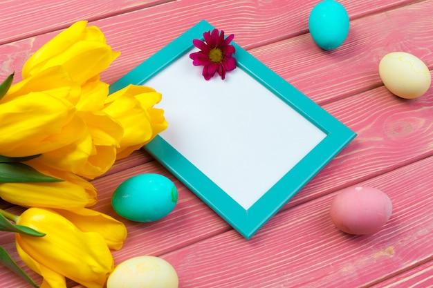 Páscoa . moldura de madeira com ovos de páscoa e tulipas em colorido Foto Premium