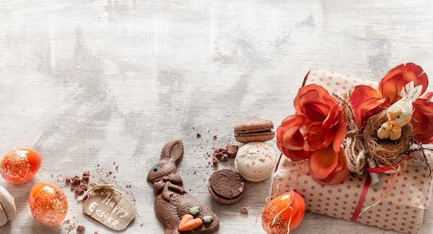 Páscoa natureza morta com presente e doces na madeira. Foto gratuita