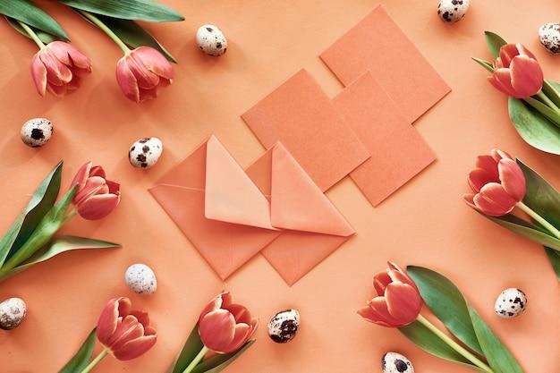 Páscoa plana leigos em papel laranja com tulipas, ovos de codorna, cartões e envelopes Foto Premium