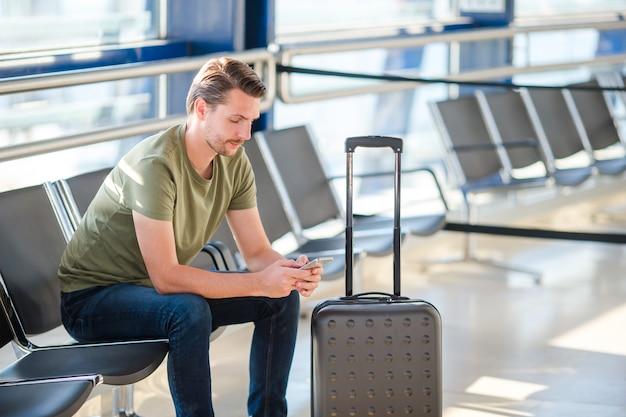 Passageiro, em, um, saguão aeroporto, esperando, para, vôo, aeronave, homem jovem, com, cellphone, em, aeroporto, esperando, para, aterragem Foto Premium