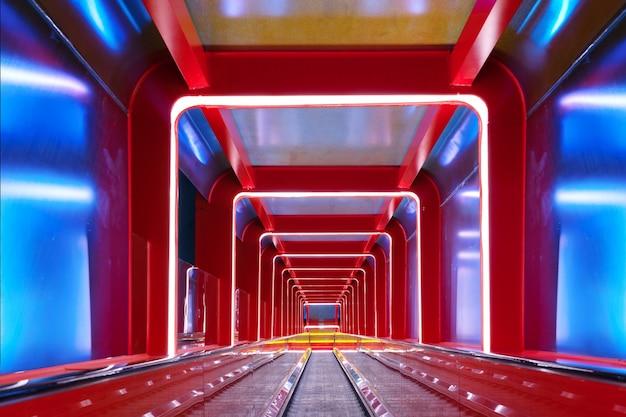 Passagem circular da escada rolante com luz vermelha Foto Premium
