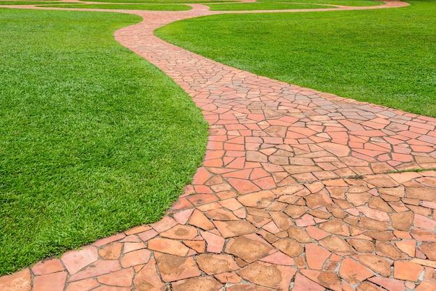 Passagem de pedra alaranjada com grama verde no parque. abstrato. Foto Premium