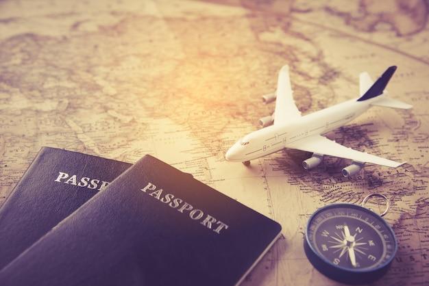 Passaporte, avião, bússola colocado no mapa -conceito de conceito Foto Premium