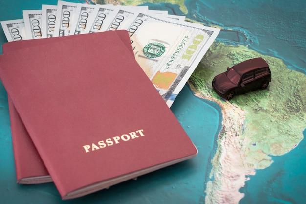 Passaporte com notas de cem dólares dentro e carro de brinquedo no fundo do mapa do mundo Foto Premium