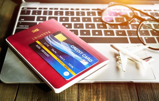 Passaporte e cartão de crédito no laptop Foto Premium