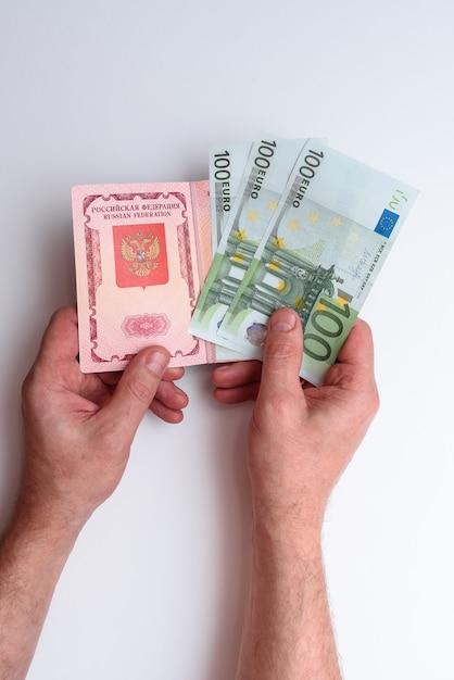 Passaporte internacional russo com euro na mão do homem Foto Premium
