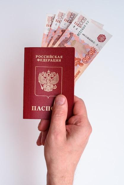 Passaporte internacional russo com rublos na mão do homem Foto Premium