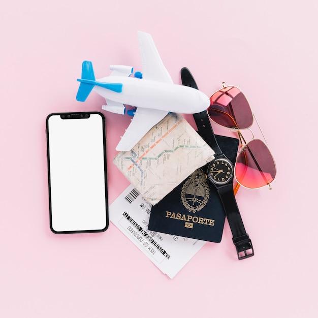 Passaporte; mapa; bilhetes; avião de brinquedo; relógio de pulso; telefone celular e óculos escuros no fundo rosa Foto gratuita