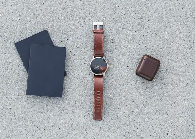 Passaportes com um relógio e fones de ouvido no fundo beton Foto gratuita