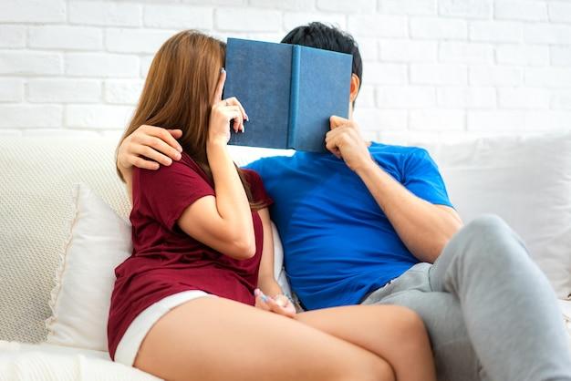 Passar bons momentos em casa. livro de leitura loving novo bonito dos pares e sorriso no sofá na sala de visitas em casa. Foto Premium