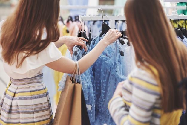 Passe algum tempo com a melhor amiga. duas mulheres às compras na loja. vista de perto Foto gratuita