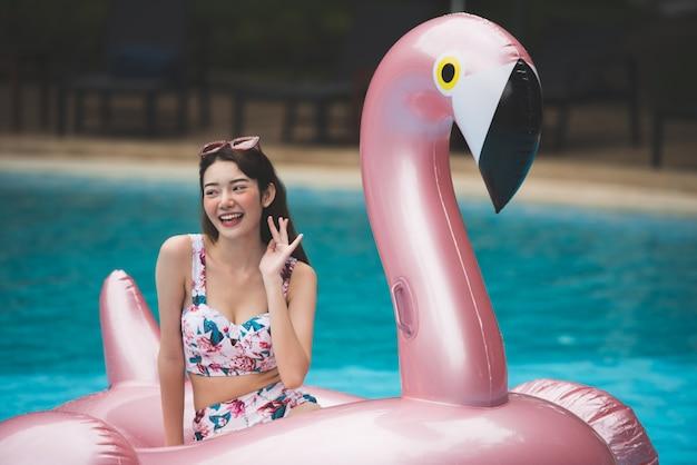 Passeio asiático novo da mulher na cisne inflável gigante na piscina. Foto Premium