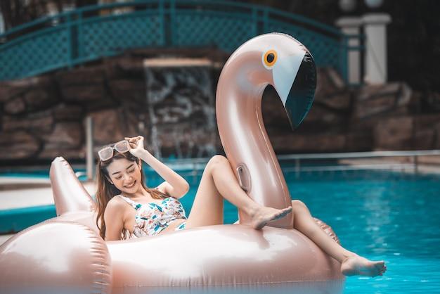 Passeio asiático novo da mulher no flamingo inflável gigante na piscina. Foto Premium