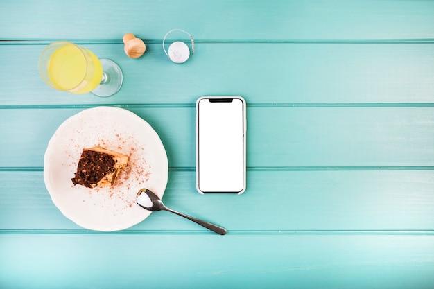 Pastelaria fresca com bebida e celular na mesa Foto gratuita