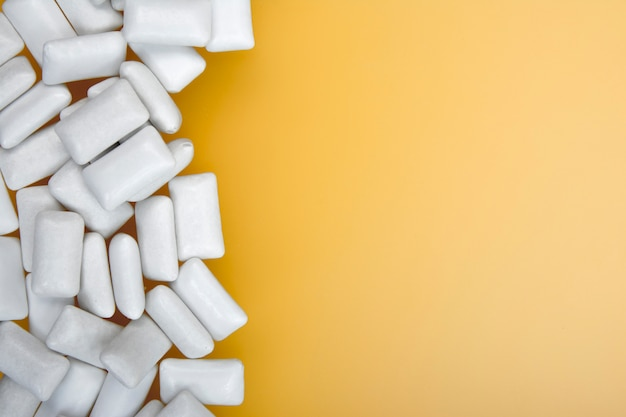 Pastilha elástica branca no amarelo com texto do espaço da cópia. postura plana. Foto Premium