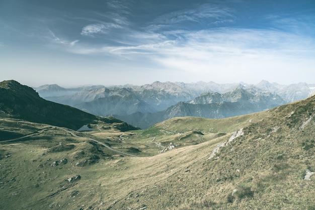 Pasto da alta altitude, picos de montanha rochosa e cume entalhado, com céu cênico, os alpes italianos. visão expansiva em luz de fundo. imagem desaturated tonificada. Foto Premium