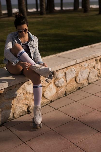 Patinadora feminina bonita, amarrando o laço de patins Foto gratuita