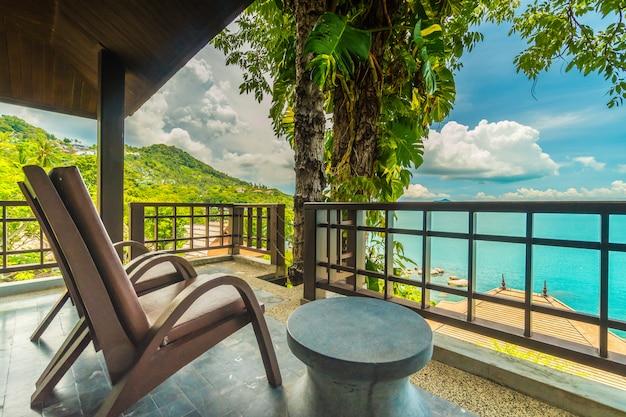 Pátio ou varanda com cadeira em torno do mar e vista para o mar Foto gratuita