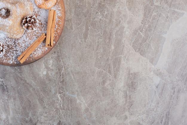 Paus de canela, biscoitos e pinhas adornando um bolo revestido de pó de baunilha sobre mármore. Foto gratuita